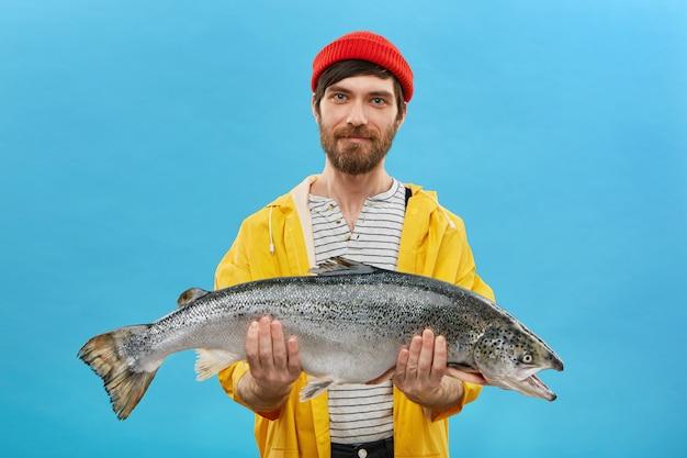 巨大な魚を手に持った黄色のアノラックと赤い帽子をかぶったひげを生やした漁師は、彼の漁獲の成功を示しています。水色の壁に大きな鮭でポーズ熟練した職人の水平方向の肖像画 無料写真