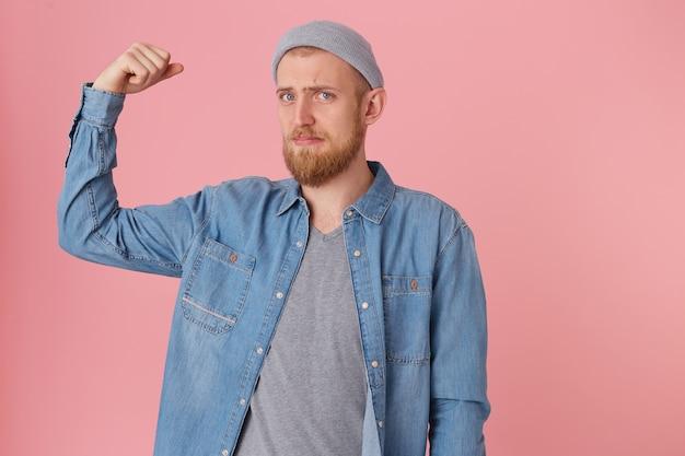デニムシャツを着たひげを生やした男は悲しそうに見え、彼の強さを自慢することはできず、彼の体型に不満を持って、彼の曲がった腕を上げて弱い筋肉を示し、悔しそうに見えます 無料写真