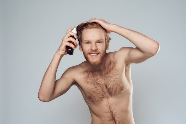 Bearded hairy man sprinkles lotion on hair at home. Premium Photo
