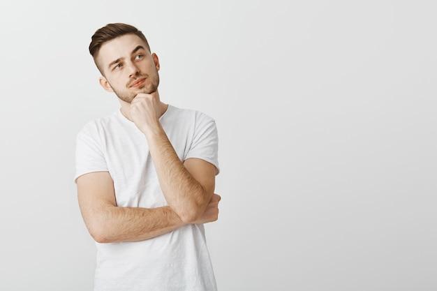 Бородатый красивый молодой человек думает, делает выбор в магазине, глядя в правый верхний угол Бесплатные Фотографии