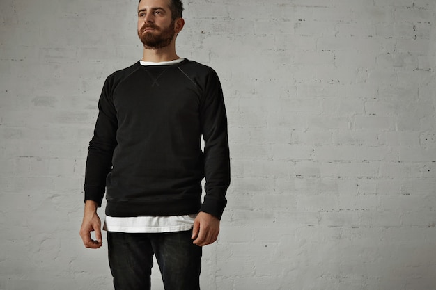 Bearded hipster wearing a blank black longsleeve shirt with a white t-shirt underneath and black jeans on white brick wall Free Photo