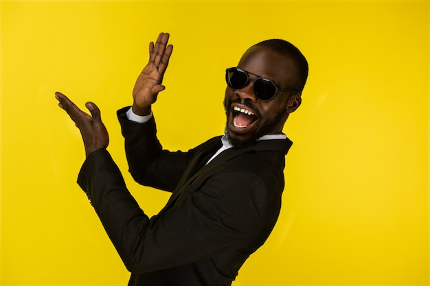 Bearded luxury young afroamerican guy is claping hands in sunglasses and black suit Free Photo