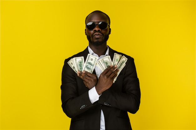 Bearded luxury young afroamerican guy is holding lots of money in both hands in sunglasses and black suit Free Photo