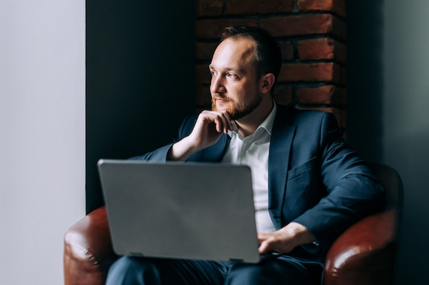 Bearded male businessman is sitting thoughtfully with a laptop in a modern interior. Premium Photo