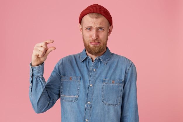 Uomo barbuto in camicia di jeans, il viso accigliato fa un gesto della mano, mostra qualcosa di molto piccolo, posa contro il muro rosa. un uomo si offre di bere una piccola quantità di liquido, per trascorrere del tempo insieme. Foto Gratuite