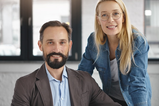 Bearded male manager in formal suit and his female assistant Free Photo