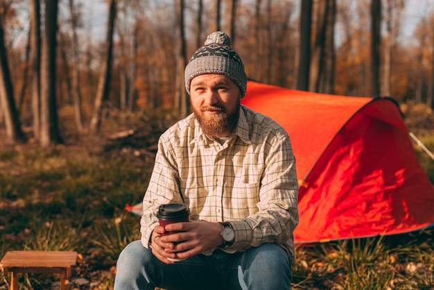 Bearded male sitting near the camping tent. young hiker man enjoy the air in the forest Premium Photo