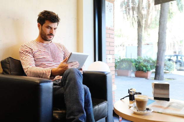 Bearded male using a tablet sitting in a sofa next to a window in a cafe Premium Photo