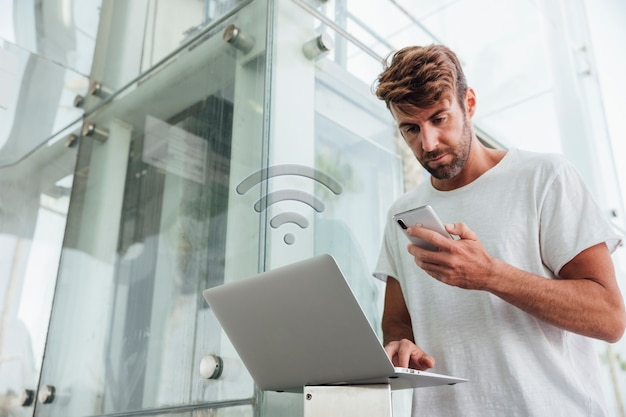 Bearded man checking portable devices Free Photo
