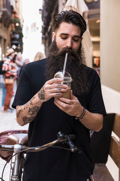 Bearded man drinking chocolate drink standing with bicycle on city street Free Photo