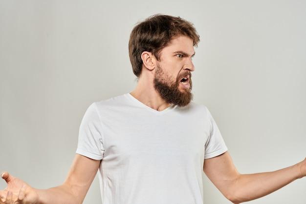 Бородатый мужчина жестикулирует руками в белой футболке агрессии светлом фоне Premium Фотографии