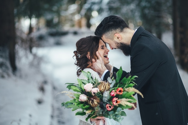 Bearded man and his lovely bride pose on the snow in a magic winter forest Free Photo