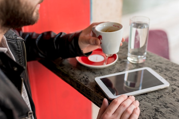 Bearded man holding cup near tablet Free Photo
