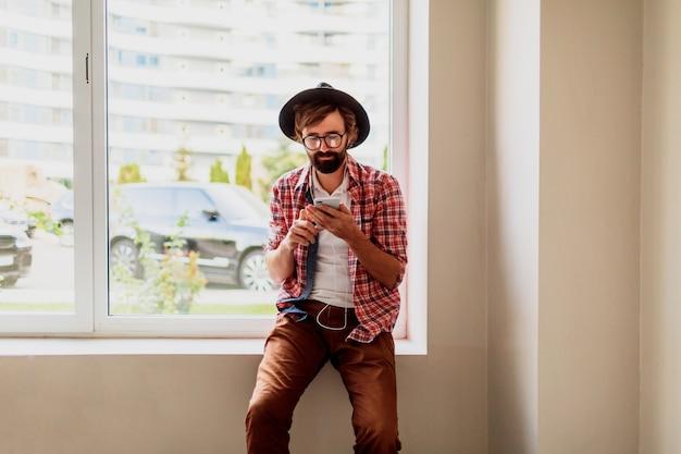 明るい市松模様のシャツを着たひげを生やした男は、スマートフォンデバイスに新しいモバイルアプリケーションをインストールして音楽を聴いています。流行に敏感なスタイル。 無料写真