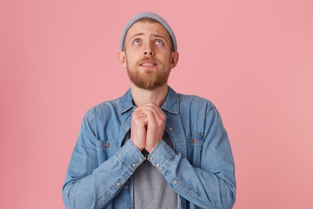 Бородатый мужчина в джинсовой рубашке и серой шляпе, желающий достичь желаемого результата, сложив руки на солнечном сплетении, изображает молитвенный жест, изолированный Бесплатные Фотографии