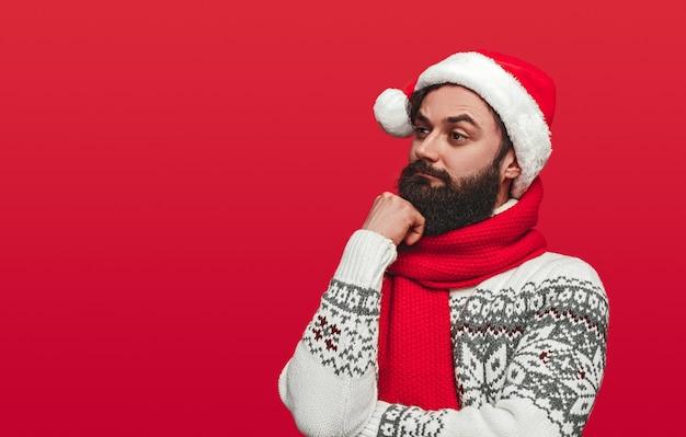 Бородатый мужчина в шляпе санта смотрит в сторону Premium Фотографии