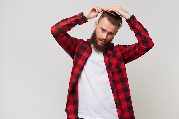 Бородатый мужчина в рубашке с не очень довольным выражением лица делает современную прическу, расчесывая волосы расческой с недовольством, изолированным на белом фоне Бесплатные Фотографии
