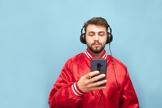 彼の手にスマートフォンで青い壁に立っているヘッドフォンでひげを生やした男 Premium写真