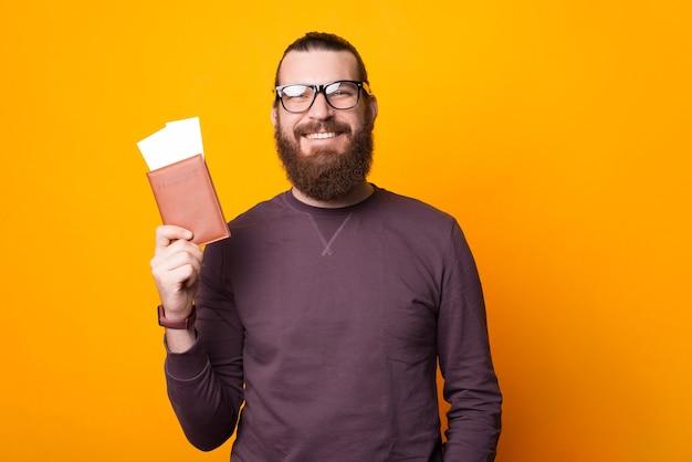 수염 난 남자는 카메라를 웃고 노란색 벽 근처에 두 개의 티켓이있는 여권을 들고 있습니다. 프리미엄 사진