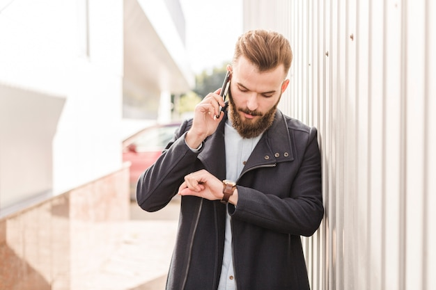 Bearded man looking at time on wrist watch while talking on cellphone Free Photo