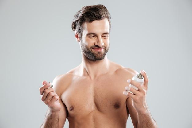 Profumo e sorridere di apertura dell'uomo barbuto Foto Gratuite