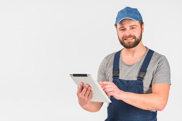 Bearded man in overall using tablet Free Photo