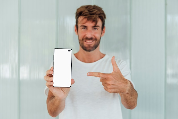 Bearded man pointing finger at phone Free Photo
