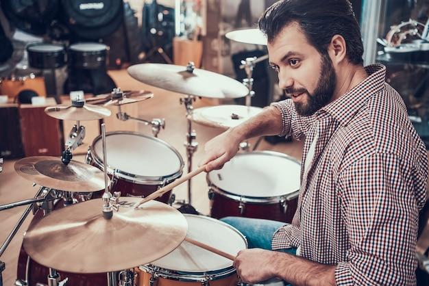 Bearded man in shirt plays on drum set. Premium Photo