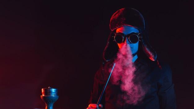 ひげを生やした男は水ギセルバーでシーシャを吸って、ネオン照明で暗い背景に煙の雲を吹きます Premium写真