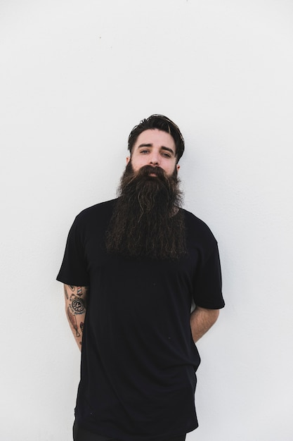 Bearded man standing against white backdrop Free Photo