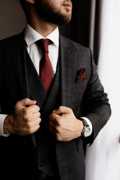 Bearded man in stylish tuxedo and red tie, strong man's hands Free Photo