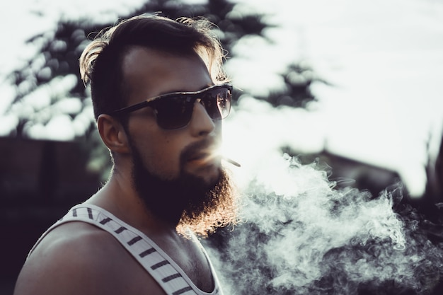 A bearded man in sunglasses smokes a cigarette at sunset, releases a thick tobacco smoke Free Photo