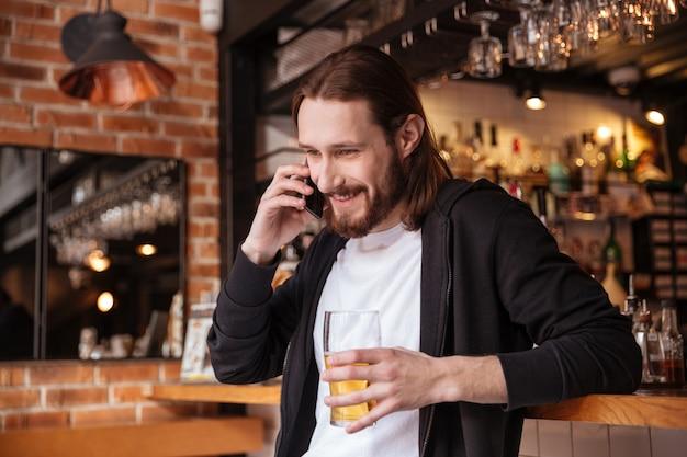 一杯のビールと電話で話しているひげを生やした男 無料写真