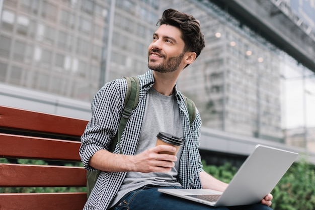 Bearded man using laptop, planning project, drinking coffee. hipster student studying outdoors Premium Photo
