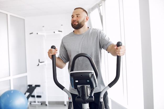 Uomo barbuto utilizzando spin bike in sala di fisioterapia Foto Gratuite