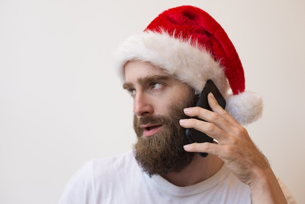 Bearded man wearing santa hat and talking on phone Free Photo