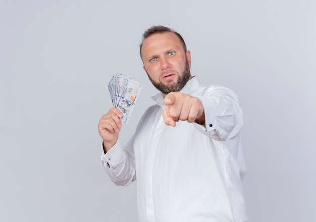 Bearded man wearing white shirt holding cash hiding money  pointign with index finger to you displeased standing over white wall Free Photo