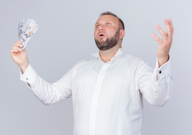 Uomo barbuto che indossa una camicia bianca che tiene contanti che osserva da parte alzando la mano in piedi sorpreso e molto ansioso sopra il muro bianco Foto Gratuite