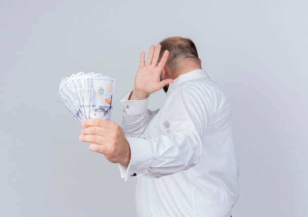Bearded man wearing white shirt holding cash making defense gesture with hand against money standing over white wall Free Photo