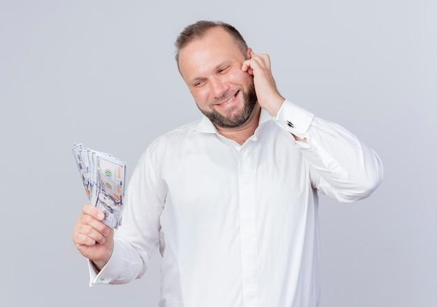 흰 벽 위에 서있는 행복한 얼굴로 웃는 현금을 들고 흰 셔츠를 입고 수염 난된 남자 무료 사진