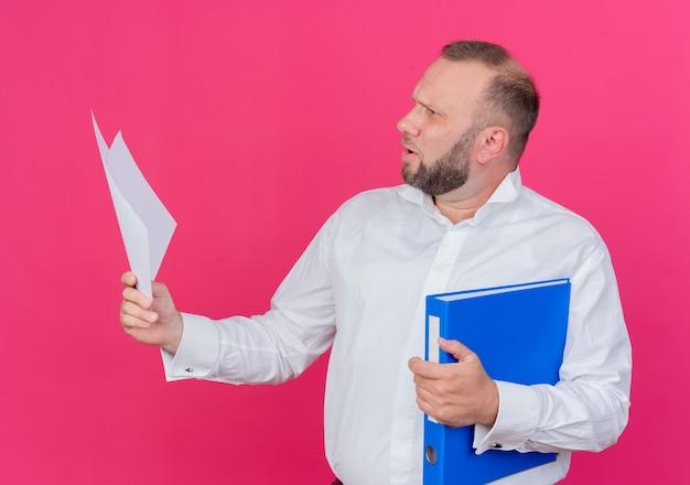 Uomo barbuto che indossa una camicia bianca che tiene cartella e fogli di carta bianca che guardano da parte confusi sul rosa Foto Gratuite