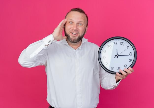 ピンクの壁の上に立って混乱した笑顔を探している壁時計を保持している白いシャツを着ているひげを生やした男 無料写真