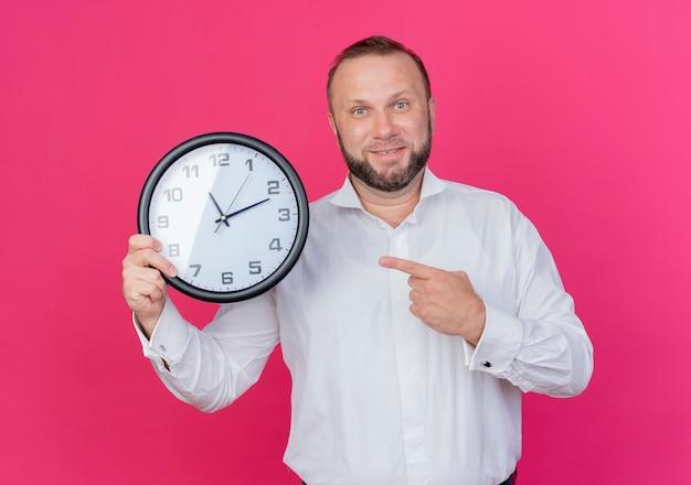 ピンクの壁の上に立って微笑んでそれを指で指している壁時計を保持している白いシャツを着ているひげを生やした男 無料写真