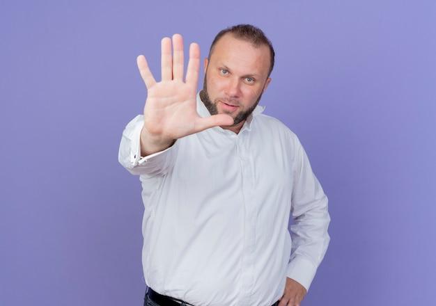 Бородатый мужчина в белой рубашке смотрит с серьезным лицом, делая знак остановки с рукой, стоящей над синей стеной Бесплатные Фотографии