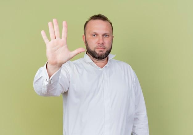 보여주는 흰 셔츠를 입고 수염 난된 남자가 가벼운 벽 위에 서있는 심각한 얼굴로보고 손가락 번호 5를 가리키는 무료 사진