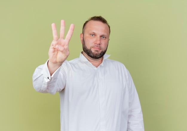 明るい壁の上に立っている真面目な顔で見ている3番目の指で上向きに見せて白いシャツを着ているひげを生やした男 無料写真