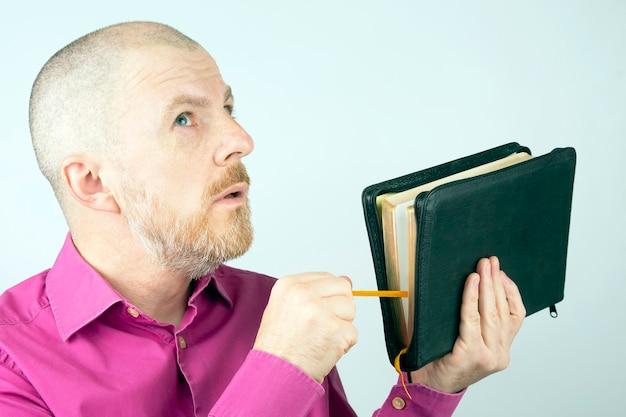 그의 손에 성경을 올려 수염 된 남자 프리미엄 사진