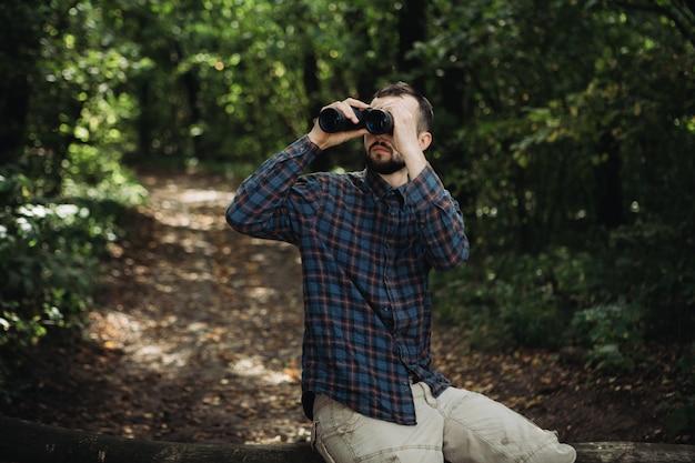 Bearded man with binoculars sitting on the branch Premium Photo