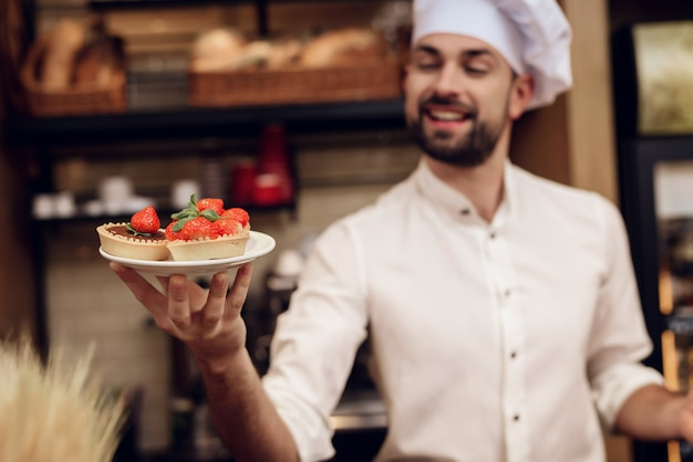 Bearded man with cake standing in bakery. Premium Photo