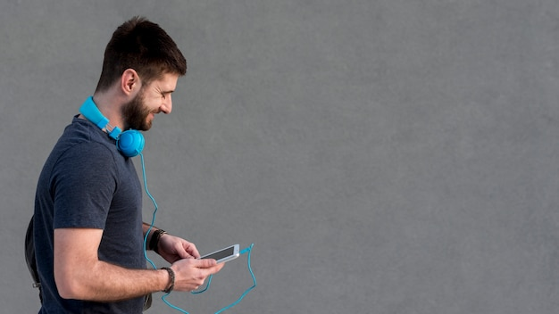 Bearded man with headphones on neck using tablet Free Photo